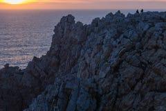 Silhouette de coucher du soleil de observation de deux personnes en mer de côte rocheuse Photo stock
