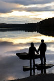 Silhouette de coucher du soleil de observation de gens au lac image libre de droits