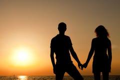 Silhouette de coucher du soleil de observation de l'homme et de femme en mer Photo libre de droits