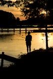 Silhouette de coucher du soleil de pêche Photos libres de droits