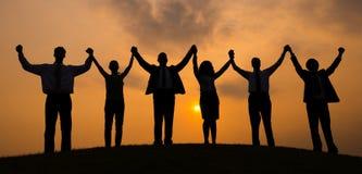 Silhouette de coucher du soleil de travailleurs d'entreprise constituée en société images stock