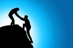 Silhouette de coup de main entre le grimpeur deux Image libre de droits