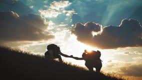 Silhouette de coup de main entre le grimpeur deux deux randonneurs sur la montagne, un homme aide un homme ? monter un pur banque de vidéos