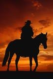 Silhouette de cowboy dans le lever de soleil Image stock