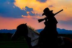 Silhouette de cowboy sur le cheval pendant le coucher du soleil gentil photos libres de droits