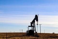 Silhouette de cric gazo-pétrolifère de pompe dans le domaine derrière la barrière de barbelé silhouettée contre le ciel bleu avec photographie stock libre de droits