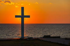 Silhouette de croix au lever de soleil ou de coucher du soleil avec les rayons légers et le panorama de mer Images libres de droits