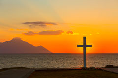 Silhouette de croix au lever de soleil ou de coucher du soleil avec les rayons légers et le panorama de mer Photographie stock