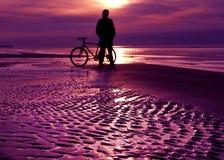 Silhouette de cycliste au coucher du soleil Photographie stock