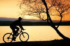 Silhouette de cycliste de jeune homme sur le fond orange rose de ciel et de coucher du soleil sur la plage Photos stock