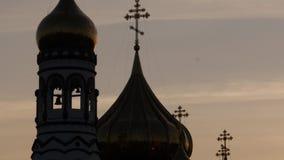 Silhouette de dôme d'or d'église sur le ciel de lever de soleil, croix chrétienne sur la tour d'église 4K banque de vidéos