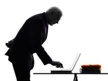 Silhouette de dactylographie de calcul supérieure d'homme d'affaires Images stock
