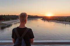 silhouette de derrière d'un type avec un fond du coucher de soleil au-dessus de l'eau de rivière images libres de droits