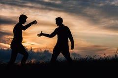 Silhouette de deux amis Images stock