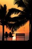 Silhouette de deux amis s'asseyant sur le banc en bois près de la plage Photos stock