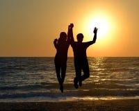 Silhouette de deux amis sautant sur la plage pendant le lever de soleil Images libres de droits
