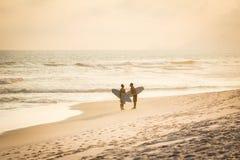 Silhouette de deux amis de surfer marchant sur la plage pendant le soleil Images stock