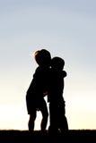 Silhouette de deux enfants en bas âge étreignant au coucher du soleil Image stock