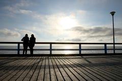 Silhouette de deux filles ou femmes sur le pont au coucher du soleil Image stock