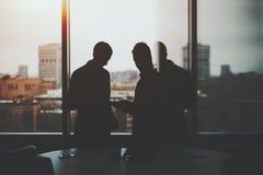 Silhouette de deux hommes d'affaires dans l'intérieur de bureau photos libres de droits