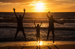 Silhouette de deux hommes et d'un garçon ayant l'amusement dans le coucher du soleil photos libres de droits