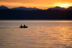 Silhouette de deux hommes ramant dans un bateau au coucher du soleil Images stock