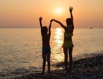 Silhouette de deux jeunes filles sur la plage de mer Images stock