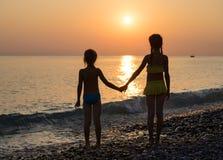 Silhouette de deux jeunes filles sur la plage de mer Photographie stock libre de droits