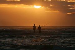 Silhouette de deux pêcheurs à la ligne contre le coucher du soleil Photos libres de droits