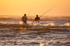 Silhouette de deux pêcheurs à la ligne contre le coucher du soleil Images stock