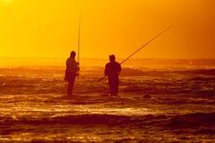 Silhouette de deux pêcheurs à la ligne contre le coucher du soleil Photographie stock libre de droits