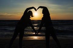 Silhouette de deux personnes dans l'amour au coucher du soleil Photos stock