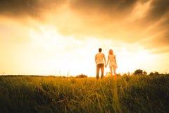Silhouette de deux personnes sur le coucher du soleil Photos stock