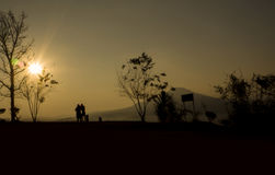 Silhouette de deux personnes sur le coucher du soleil Photo stock