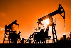 Silhouette de deux pompes de pétrole Images stock