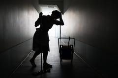Silhouette de domestique féminine avec le balai Photos stock