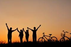 Silhouette de famille avec la bicyclette sur le champ d'herbe Photo stock