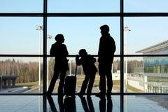Silhouette de famille avec le bagage près de l'hublot Images stock