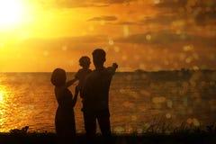 Silhouette de famille dans le coucher du soleil extérieur Images stock