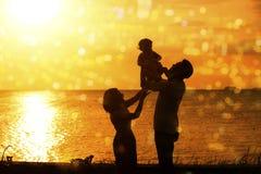 Silhouette de famille dans le coucher du soleil extérieur de plage Image libre de droits