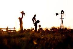 Silhouette de famille dans le domaine avec le moulin à vent Image stock