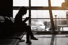 Silhouette de femme à l'aéroport avec le téléphone portable et le backpac Photo stock