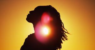 Silhouette de femme africaine se tenant au coucher du soleil Image libre de droits