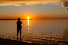Silhouette de femme au coucher du soleil de plage photo stock