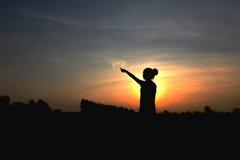 Silhouette de femme au coucher du soleil, posture debout, près de faible Photos stock