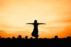 Silhouette de femme au coucher du soleil, yoga de jeu de femme Images stock
