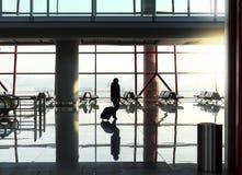 Silhouette de femme avec le bagage contre de grandes fenêtres Image libre de droits