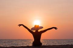 Silhouette de femme avec le chapeau se reposant sur le fond de mer Photo stock