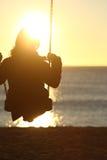 Silhouette de femme balançant au coucher du soleil sur la plage Image stock