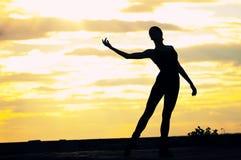 Silhouette de femme de danse au-dessus de coucher du soleil. Yoga Images libres de droits